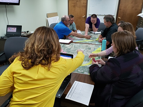Picture of people looking over floodplain maps on a table.