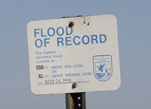 """Sign: """"Flood of Record 858 ft above sea level or 10 ft above ground level on July 24, 1993"""""""