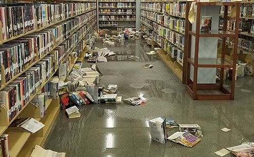 Wet library books displaced off bottom shelves by floodwaters.