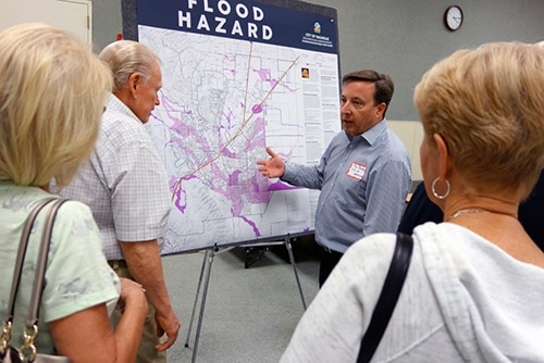 People standing at a poster-size map of flood hazard.